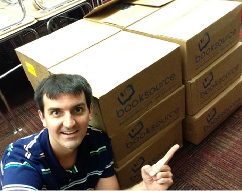Dowling High School English Teacher Austin Hall poses with the books he received from the Book Love grant.
